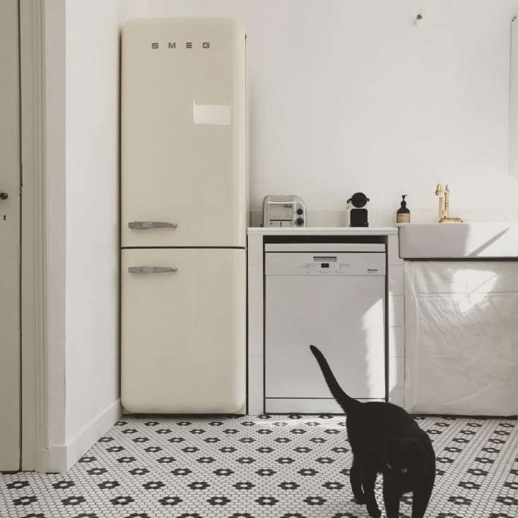 "The ""back kitchen,"" with a newly laid black and white tile floor and cream-colored Smeg fridge. Notice the simple sink skirt."