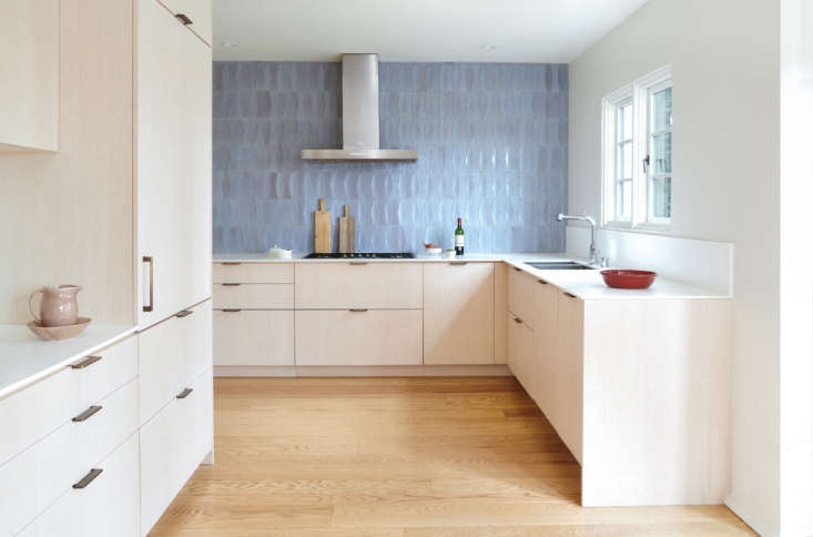 """Each room is defined by one attention-grabbing detail; in the kitchen it's the locally made Heath Bowtie and Diamond-shaped dimensional tiles in a glaze called frost that allows the clay to subtly show through. """"I wanted a wall with no upper cabinets, just a dramatic backsplash that you can see from the living room,"""" says Stéphanie. """"It's a backdrop to the openness of the general living space,"""" adds Kristen."""