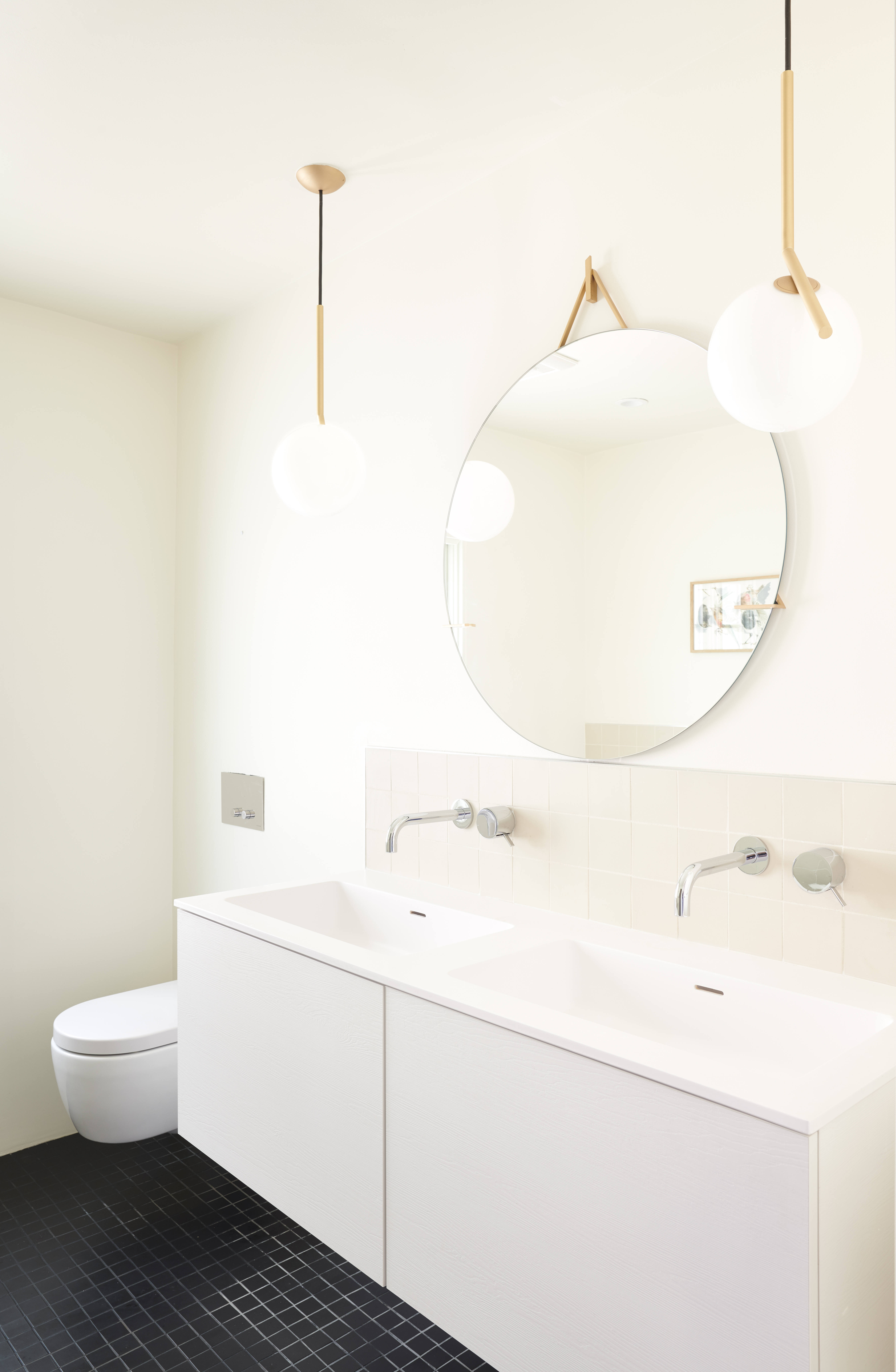 """The dressy black-and-white master bath is lit by Michael Anastasiades's IC Lights S2for Flos. The sink vanity and wall-hung toilet are fromBlu Bath Works(""""suspended toilets were a must for a light and airy line,"""" says Stéphanie, """"the cabinets and countertops are minimalist and echo the kitchen design""""). The unglazed white backsplash tiles and square black floor tiles are from Heath. The mirror is by Egg Collective."""