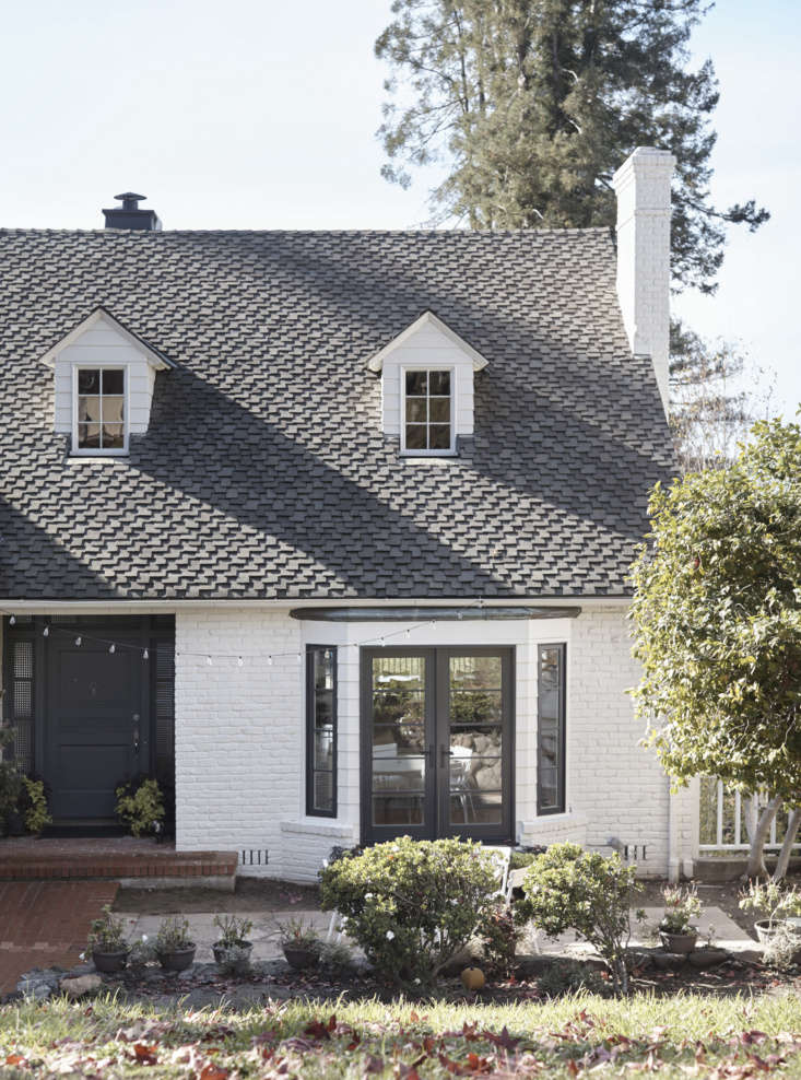 """The red brick exterior—with its original slate roof—was given a fresh guise courtesy of white paint and black-framed windows, including new French doors in the bay window. """"My inspiration for the cottage style look was from the North of France, where I grew up,"""" saysStéphanie."""