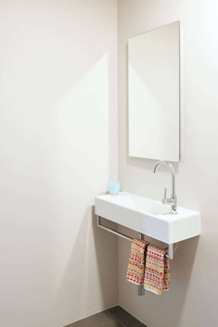 The powder room's slim, wall-mounted sink with towel bar is an Alape design sourced from Jack London, and the faucet is by Fantini.