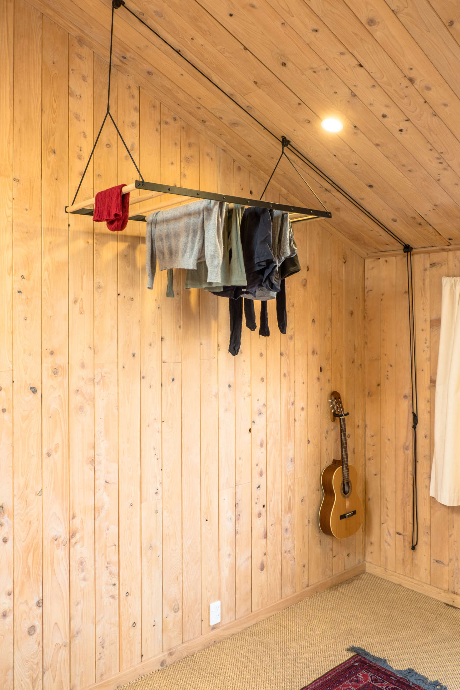 A George & Willy pulley system drying rack hangs in a corner of the master bedroom where it takes up little space and allows clothes to dry in the warmest air. Read about the design in Object of Desire: A Hanging Laundry Rack.