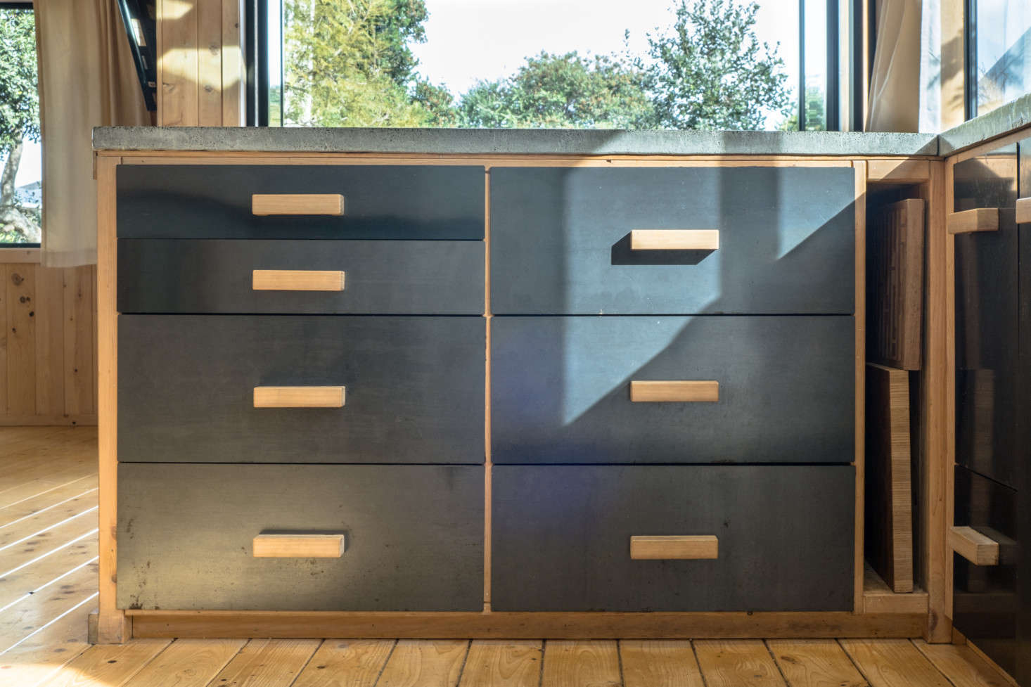 The steel-fronted drawers have handmade wooden pulls. In hindsight, George says, it would have been more cost-effective to buy kitchen cabinets than to build them: