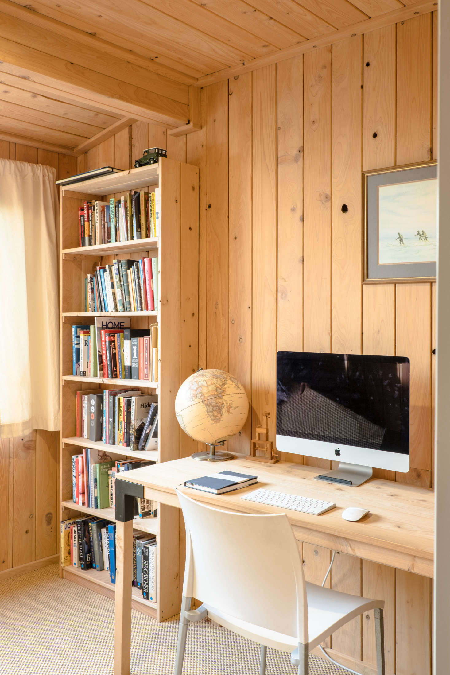The fully paneled office has a desk and bookshelf that George fabricated from leftover macrocarpa exterior cladding. He says he