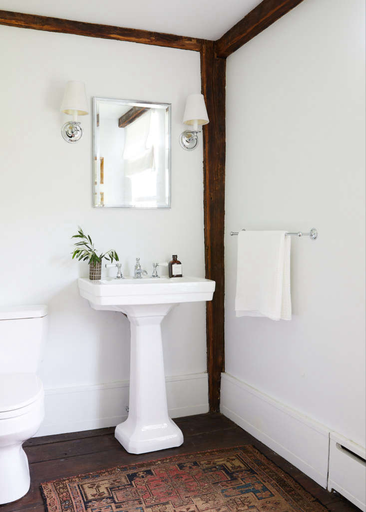 The simple bath is outfitted with traditional Waterworks fixtures.