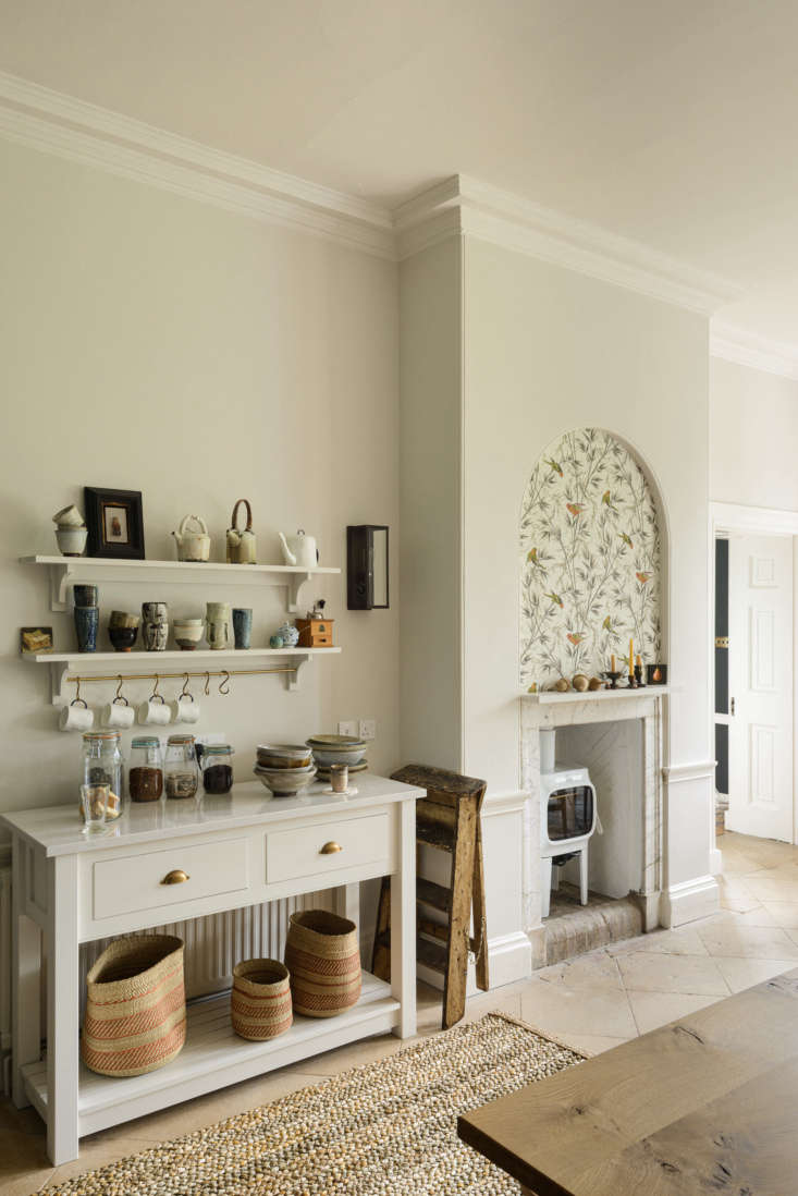 """Across from the island is a console set up for tea-making. Whimsical wallpaper by Little Greene Paint & Paper (in """"Great Ormond Street"""" pattern) adds a decorative note to the original fireplace."""