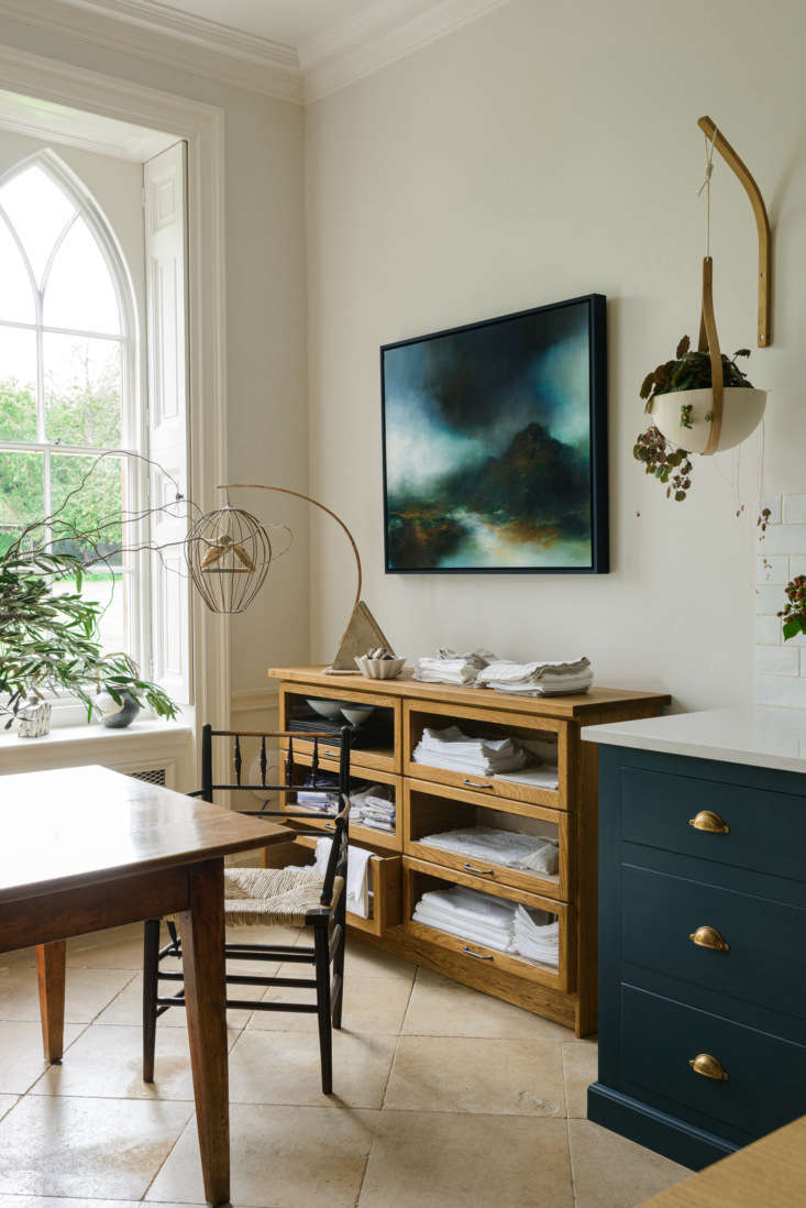 The glass sideboard, for storing kitchen linens, is from deVOL's Haberdasher's Kitchen series. The Morvah Hanging Planters are by Tom Raffield.