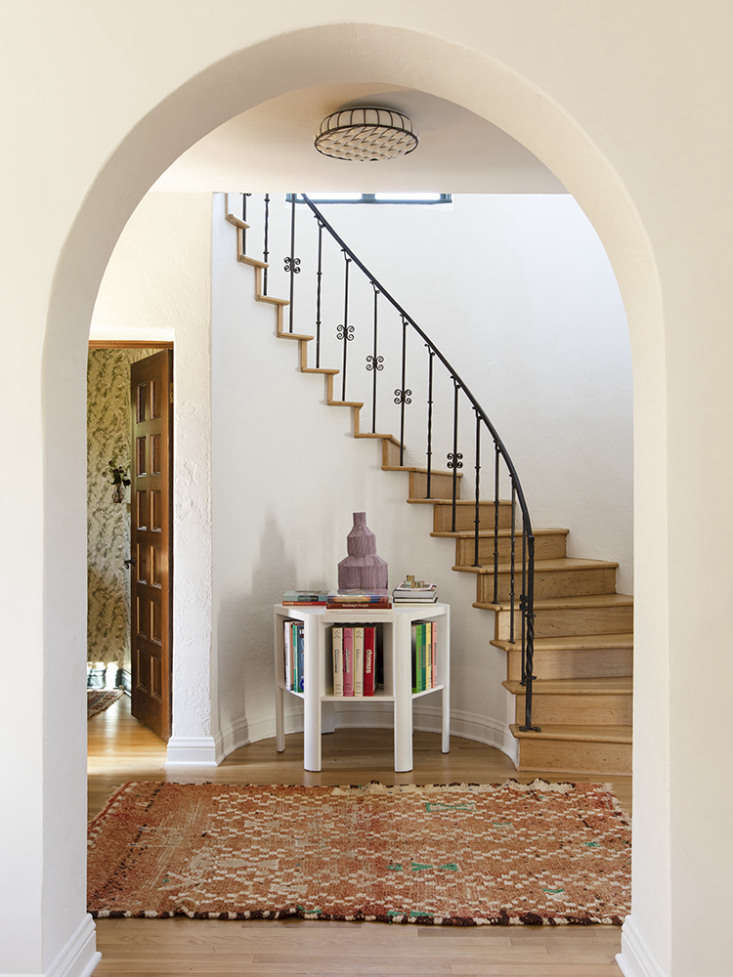 a martin & brocket library table stands in the entry under a curved stair.  10