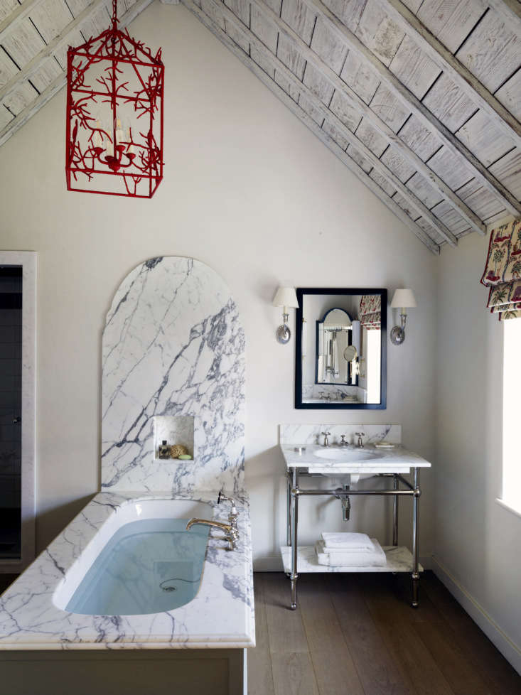 Bathroom with marble surround and curved backsplash, designed by Beata Heuman for a Sussex cottage.