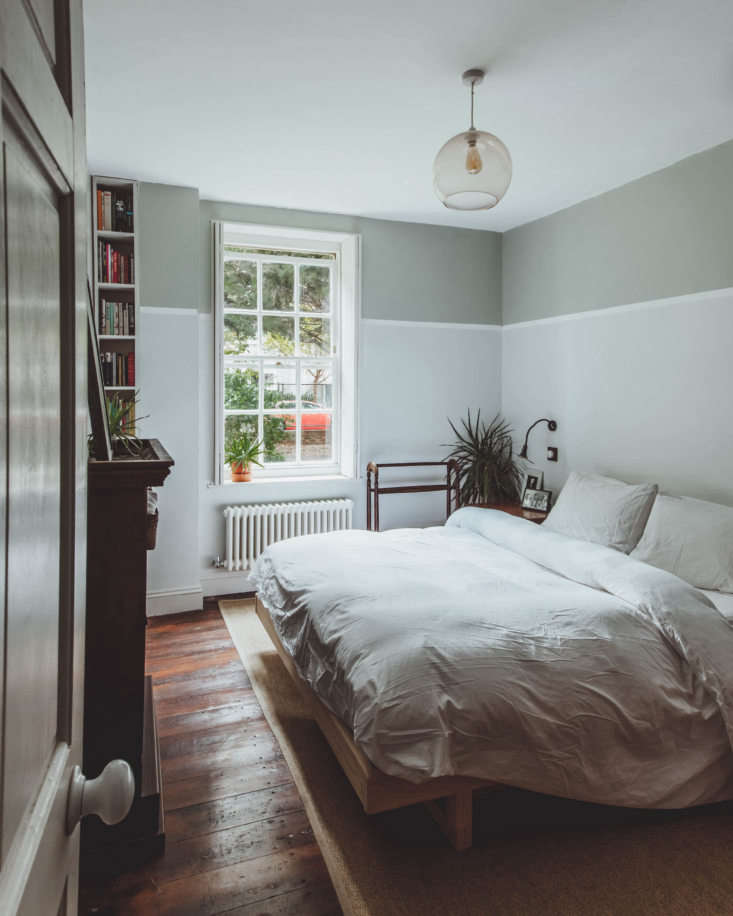 in the bedroom, dark stained floors and a simply made bed. 16