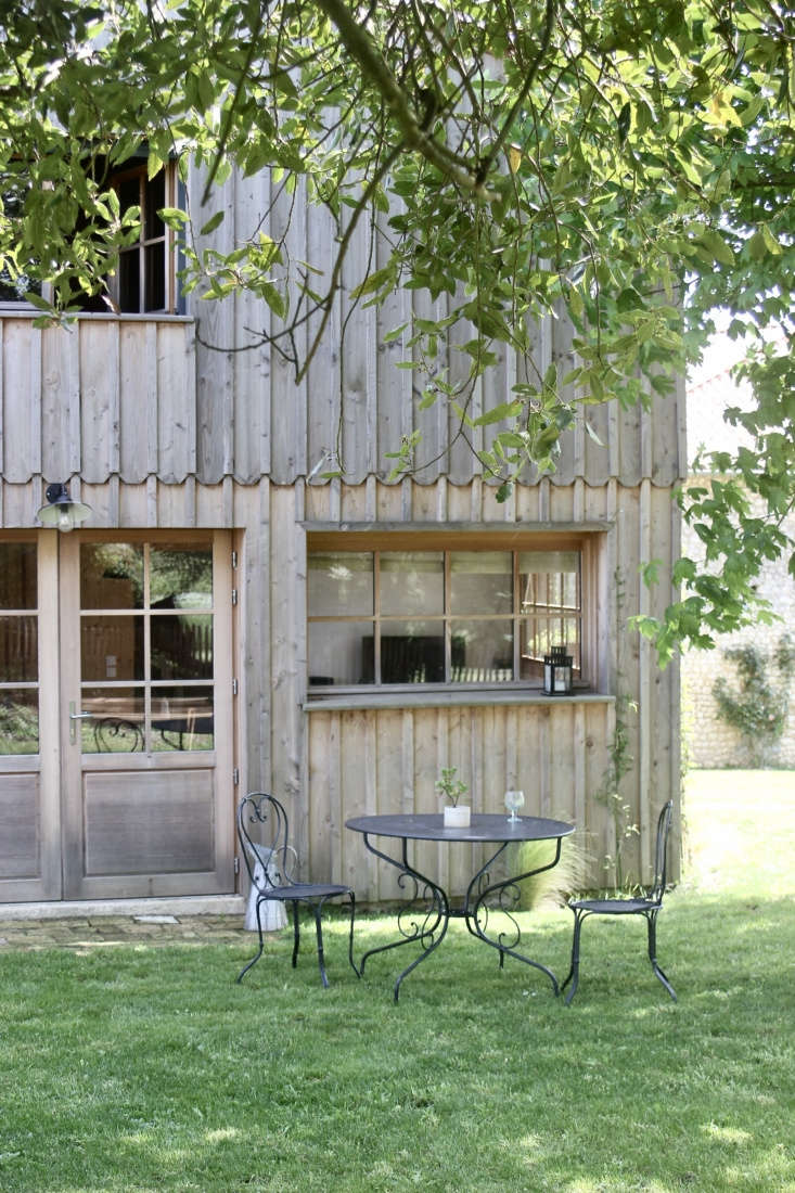 A table for two aside a board-and-batten cottage inspired by the fisherman's houses of Cap Ferret. Photograph by Jean Hay de Slade, courtesy of Epure, from Creative Compound: A Ceramic Artist Couple at Home and Work in the French Countryside.