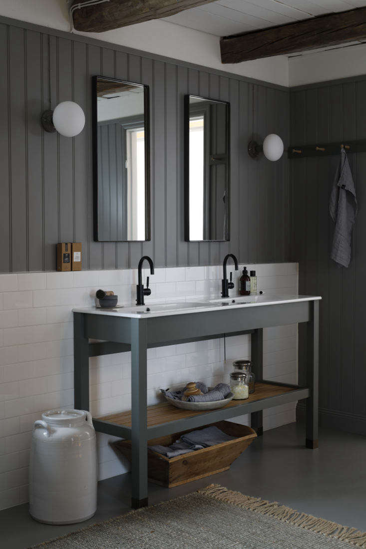 Steal This Look A Dream Dressing Room from Sweden Italian sinks with Dornbracht Tara faucets are set in a Kvänum vanity with slatted storage. The subway tiled backsplash meets beadboard paneling in a warm gray from Norwegian paint company Jotun (NCS code 6502 Y). Contemplating your own beadboarding? See Remodelista 101: The Ultimate Guide to Shiplap, Beadboard, and V Groove Paneling.