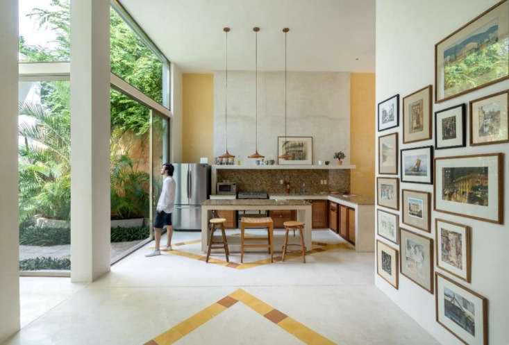 An entire glass wall in the kitchen of this Mexican home offers a generous view of the courtyard patio. Photograph by Apertura Arquitectónica, courtesy of Taller Estilo Arquitectura, from Casa Cool: A Couple's Secret Sanctuary in Mexico's Colonial City of Mérida.