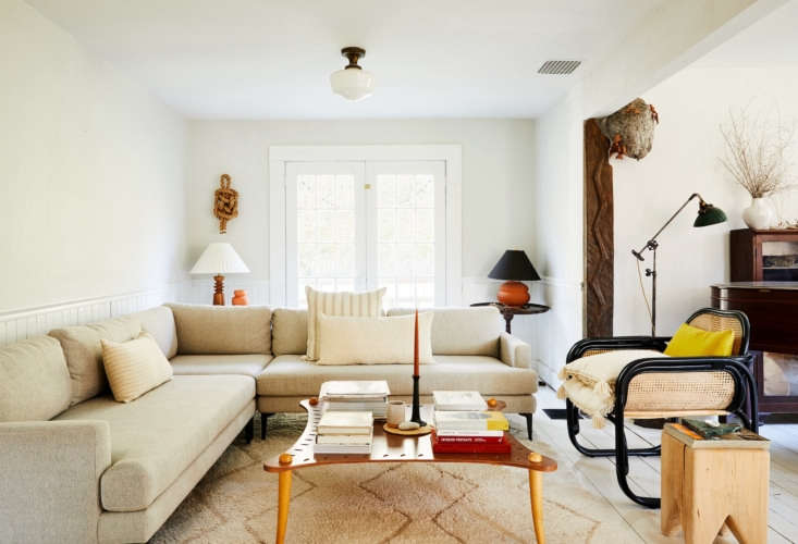 a persimmon candle takes center stage in the eclectic, layered living room of w 14