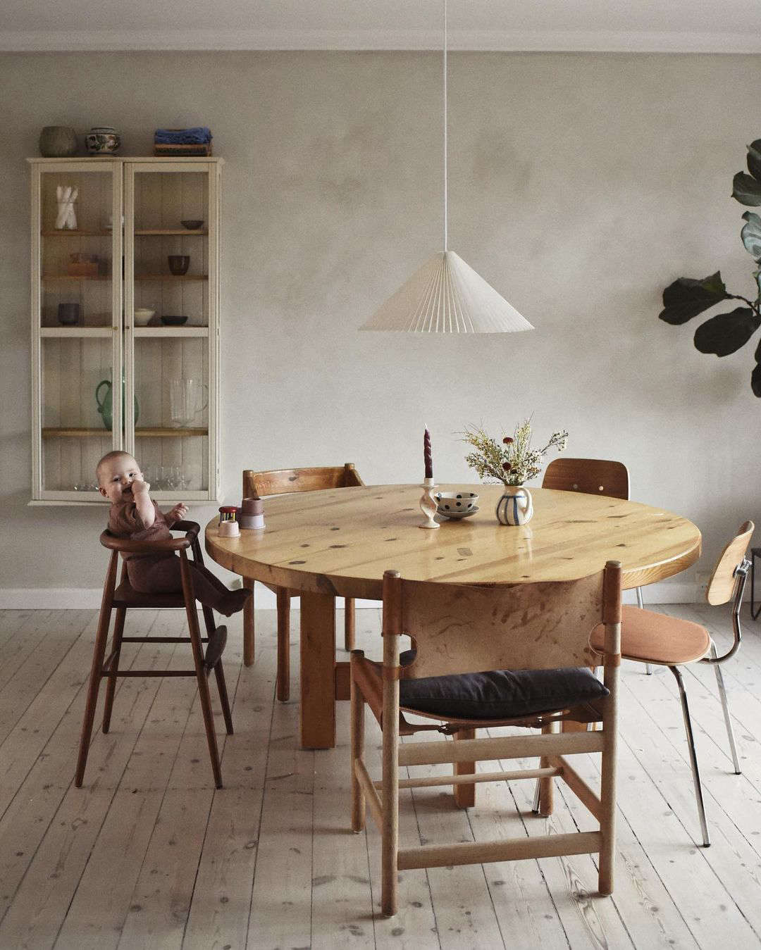vintage seating, including a vintage high chair, surround a sturdy pine table. 9