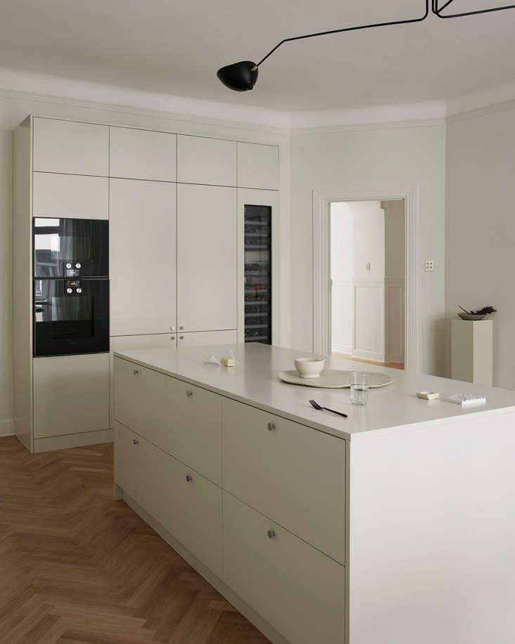hidden from the living room view is a wall unit that conceals the refrigerator  16