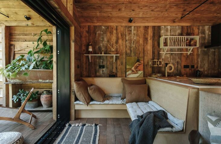 Tour this charming one-bedroom cabin built from salvaged materials in Retreat for Two: A Lakeside Rental Cabin at Settle in Norfolk, England. Photograph by India HobsonofHaarkon, courtesy of Settle (@settlenorfolk).