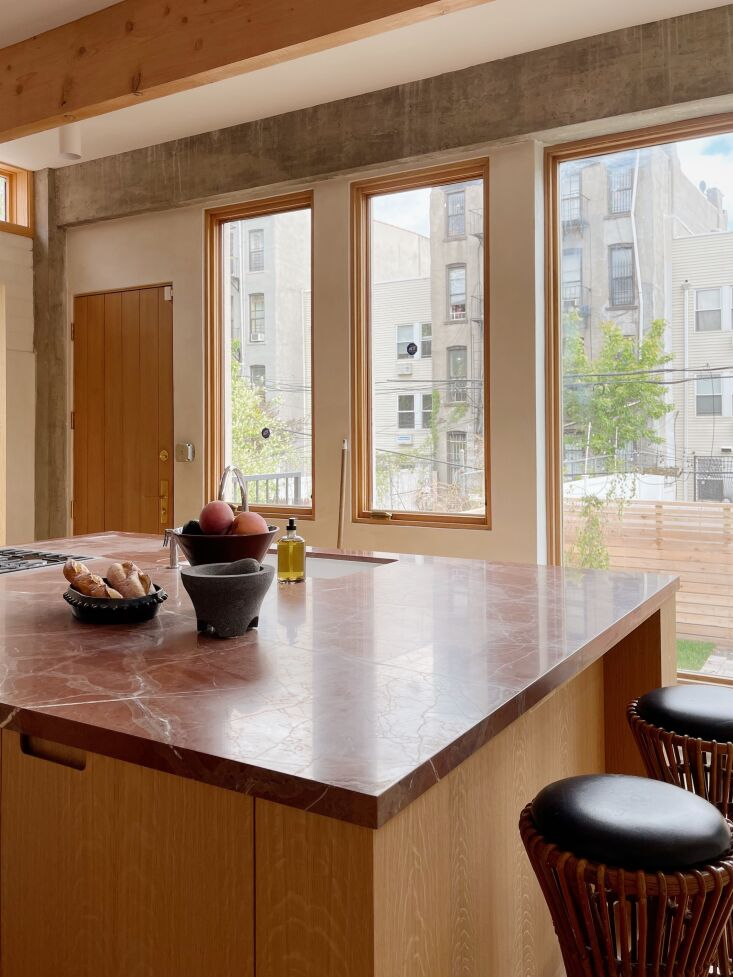 The custom millwork is oak topped with Rosso Collemandina marble. The \1960s counter stools are by Tito Agnoli. Photograph by Hollister Hovey.