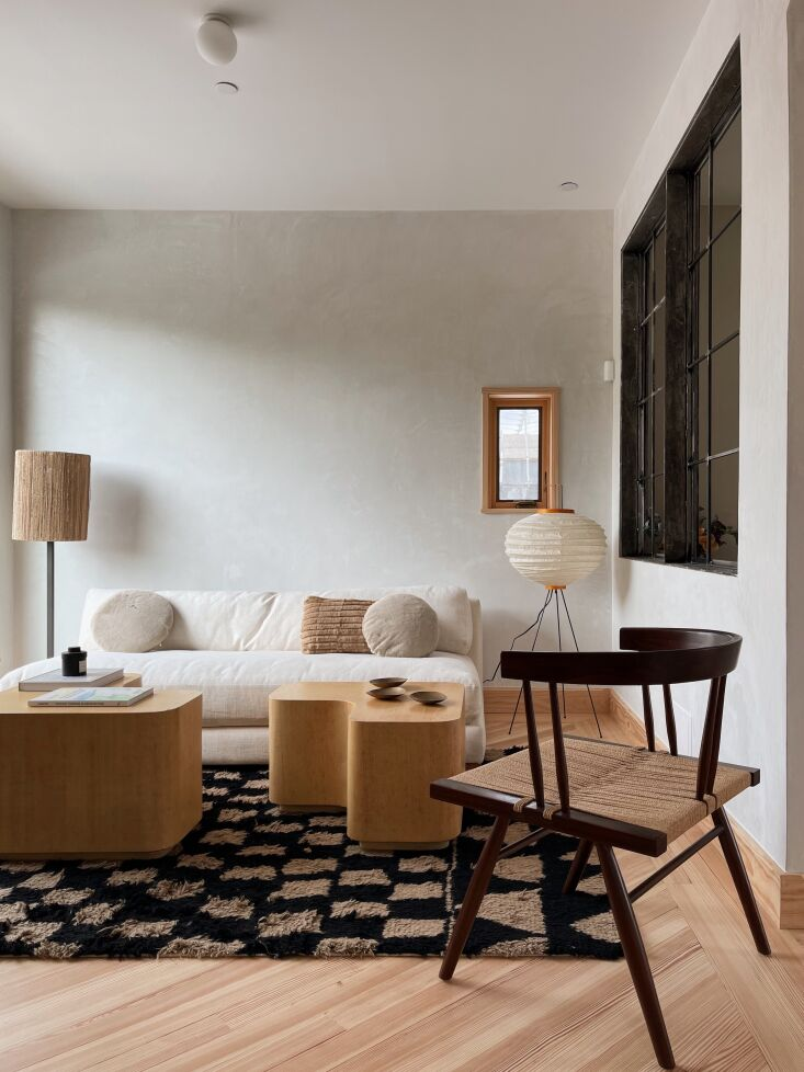 The sitting area is furnished with a CB\2 sofa and Madeline Weinrib rug from ABC Carpet . The interior steel windows bring light into the bath. Photograph by Hollister Hovey.