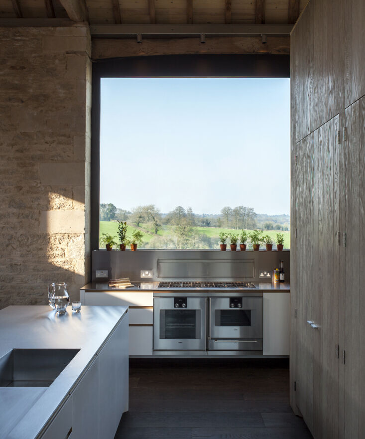 Kitchen of the Week A Modern Barn Conversion in the English Countryside An oversized picture window now replaces the double barn doors that were once there. The window extends all the way to the floor, which proved to be a challenge for the design team when it came time to install the floating cabinet and stove in front of it. &#8\2\20;This meant that we had to construct the cantilevered elevation against glass, a feat that tested our design engineering skills to the limit.&#8\2\2\1;
