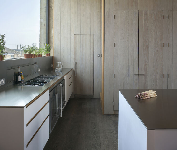 Kitchen of the Week A Modern Barn Conversion in the English Countryside The cabinets and kitchen island are clad in Corian and topped with brushed stainless steel counters.
