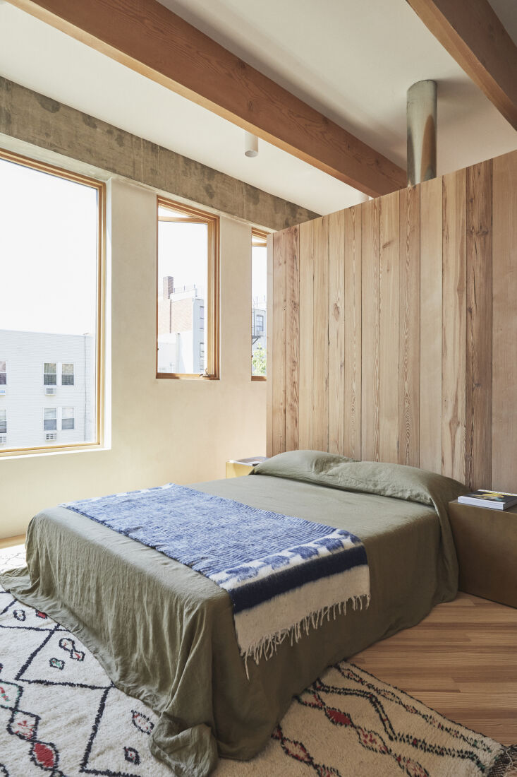 The bedroom is sectioned off from the closet by a paneled wood divider—a combination of reclaimed Southern Yellow pine and Douglas fir—that doubles as a headboard. The house&#8\2\17;s natural wood tones and &#8\2\20;emphasis on warm hues,&#8\2\2\1; came from the architects&#8\2\17; travels in Spain and Portugal just before they started working on the project.