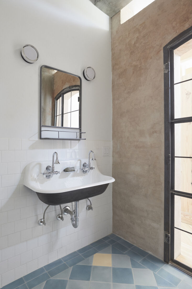 The bath has a double utility sink—the wall-mounted Brockway from Kohler with Kohler&#8\2\17;s Triton Bowe gooseneck spouts—and a floor of cement tiles from Villa Lagoon Tile of Gulf Shores, Alabama.