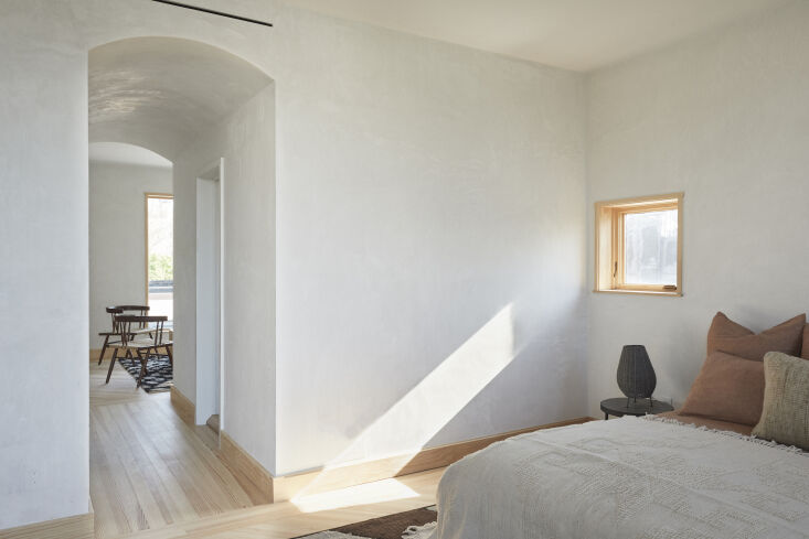The new-construction top floor was conceived as a private aerie with its own arched passageways. The window surrounds are clear white pine left raw.
