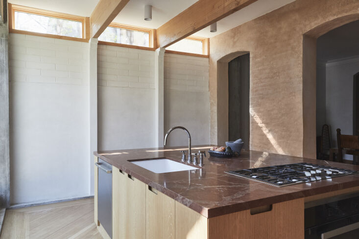 &#8\2\20;The kitchen design is centered on a large island, placing emphasis on the rich red stone surface and the idea of a large, communal gathering spot in an otherwise spartan space,&#8\2\2\1; says Bretaigne. Note the extension&#8\2\17;s Douglas fir beams and clerestory windows.