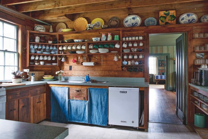 Required Reading A Glimpse Inside The Maine House The wood clad kitchen is fitted with ad hoc cotton curtains in lieu of cabinet doors, sewn by Jim&#8\2\17;s wife, Maudie.