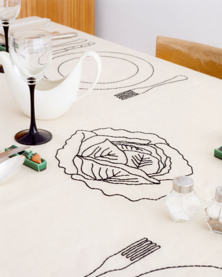 """The design features """"four plates, one cabbage, one baguette, one butterfly, one bottle of wine, and one snail."""""""