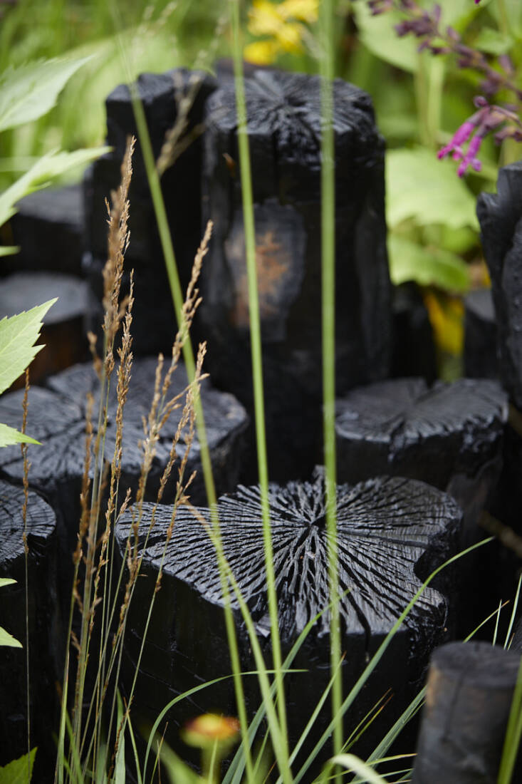 One of the most exquisitely beautiful details on the garden are the charred logs that are used vertically throughout to create mini walls of extreme beauty, each one an intricate map of deep black fissures.